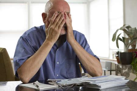 paying the bills: Older man paying bills, horizontal