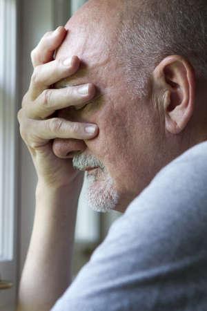 elderly man: Older man expressing pain or depression, vertical