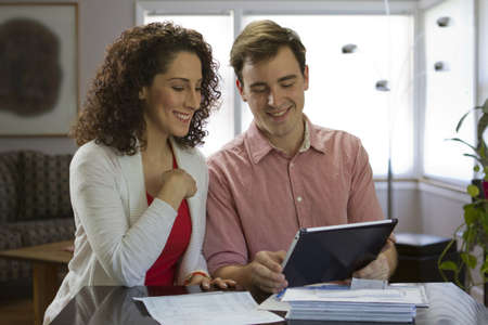 Couple using tablet and going over bills, horizontal