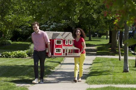 puppenhaus: Junges Paar bewegt Puppenhaus, horizontal