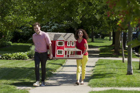 Young couple moving dollhouse, horizontal Stock Photo - 21211239