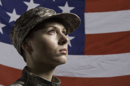 military uniform: Young military woman pictured in front of US flag, horizontal Stock Photo