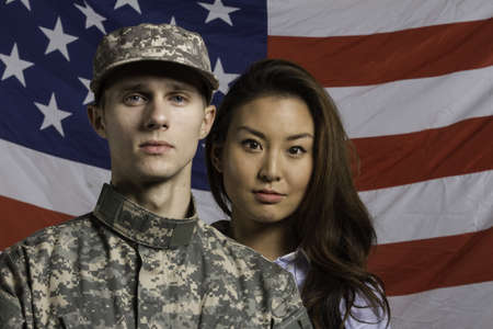 Military man and his wife in front of US flag, horizontal