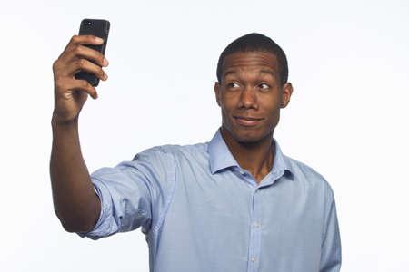 tomando: Homem Africano-Americano jovem tirar uma foto de si mesmo com smartphone, horizontal Banco de Imagens