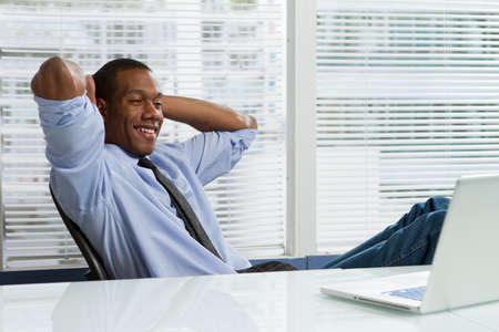 Young African-American business man taking a break at his desk, horizontal