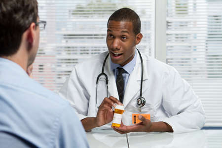 Doctor consulting with patient and holding prescription bottle, horizontal photo