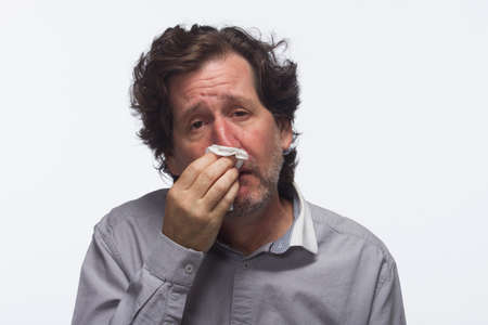 Sick man with tissue, horizontal