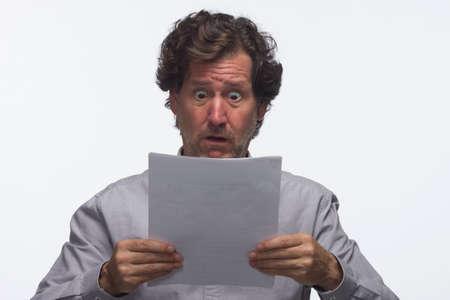 Business man looks surprised as he reviews report, horizontal
