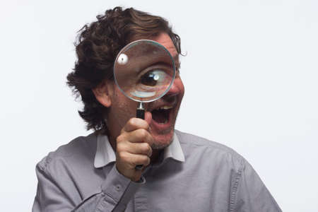 Smiling man with magnifying glass, horizontal