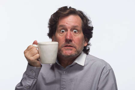 Jittery man with cup of coffee, horizontal