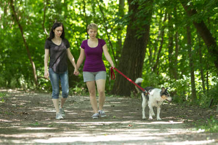 Girlfriends walking dog together at park, horizontal