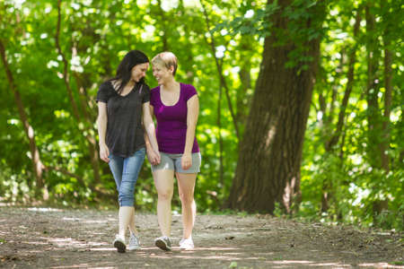 beautiful lesbian: Girlfriends holding hands and walking in park, horizontal Stock Photo