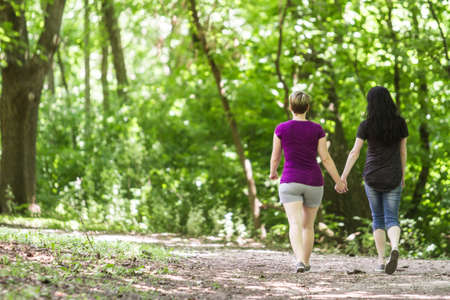 lesbianas: Girlfriends caminar juntos en el parque, horizontal