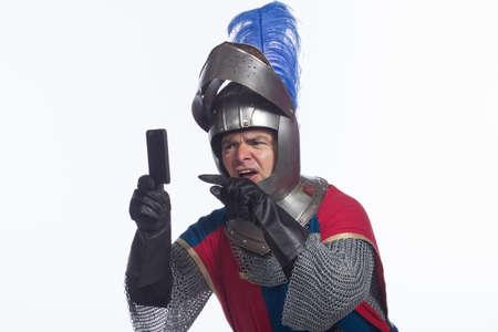 Confused knight using smartphone, horizontal photo