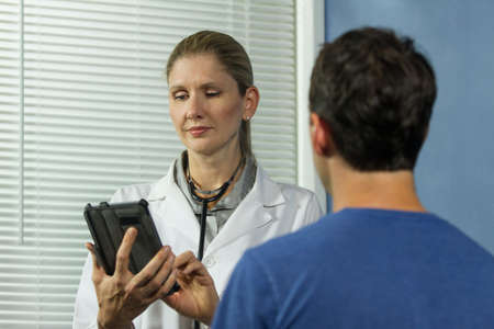 Female doctor typing into e-tablet, horizontal
