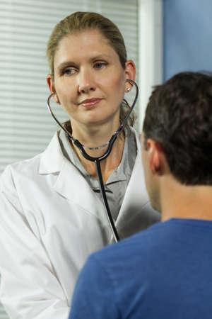 Vrouwelijke arts met mannelijke patiënt, verticaal