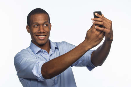 Young African American man taking selfie picture with smartphone, horizontal photo