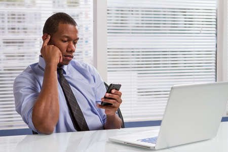 African American businessman at desk using smartphone, horizontal photo
