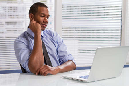 Black businessman at desk reading emails, horizontal photo