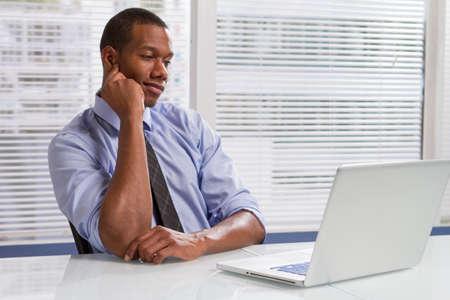Black businessman at desk reading emails, horizontal Stock Photo