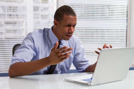 水平彼コンピューターのモニター上の項目に反応してビジネスマンを動揺します。 写真素材