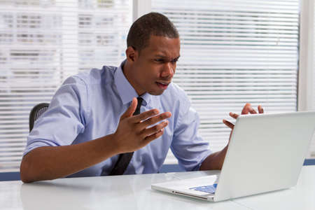 Upset businessman reacting to items on his computer monitor, horizontal