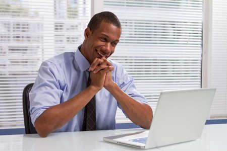 Afro-Amerikaanse zaken man glimlachen en kijken naar laptop, horizontale