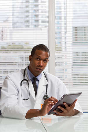 African American doctor with tablet, vertical photo