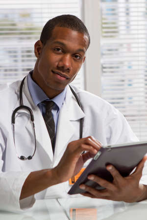 African American doctor with tablet, vertical Stock Photo