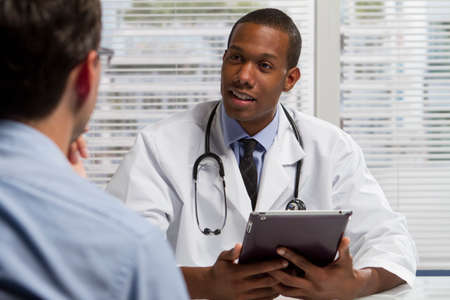 patient: Black doctor with patient and using electronic tablet, horizontal Stock Photo