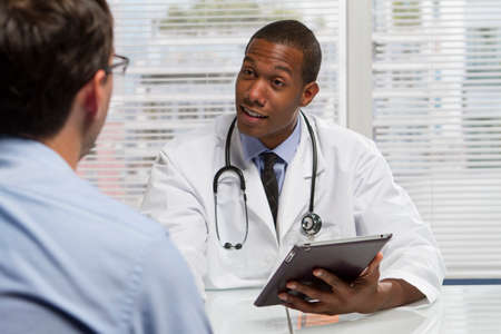 Black doctor with patient and using electronic tablet, horizontal photo