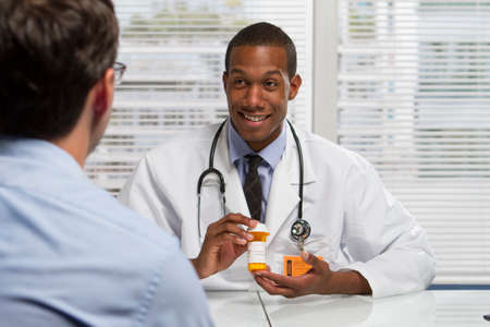 Young black doctor showing patient prescription, horizontal photo