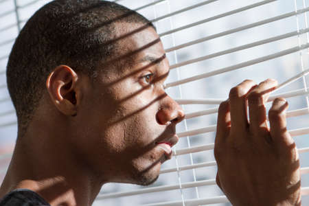Young black man looking out window, horizontal photo