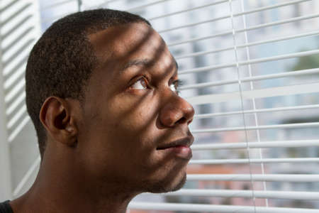 Young African American man looking out window, horizontal photo