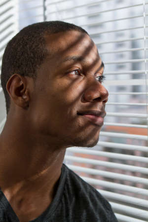 Young African American man looking out window, vertical photo