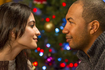 Couple leaning in and looking at each other in front of Christmas tree, horizontal photo