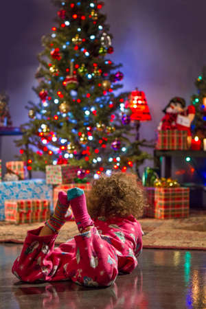 christmas morning: Little girl staring at Christmas tree, vertical