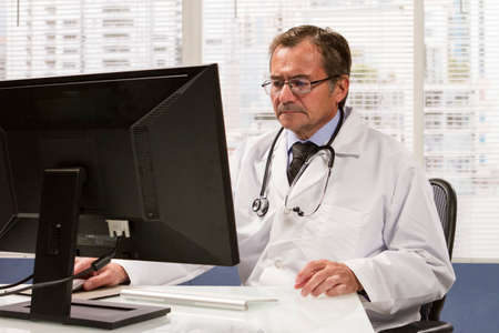 Doctor using computer in his office, horizontal Stock Photo