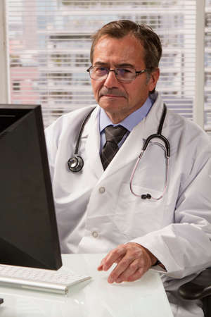 Doctor looking up information on computer, vertical photo