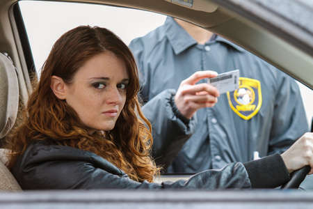 pulled: Young woman looks away from cop after being pulled over, horizontal Stock Photo