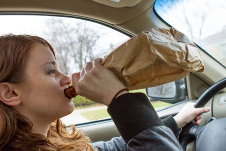 Young woman drinking and driving, horizontal Stock Photo