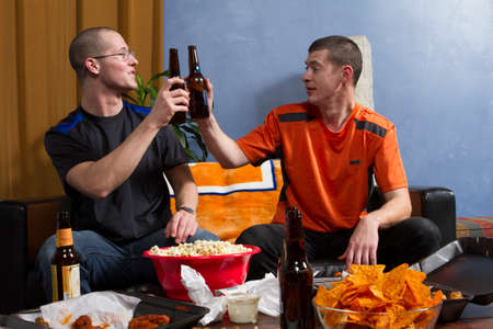 Two men cheering with beers while watching sports game on TV