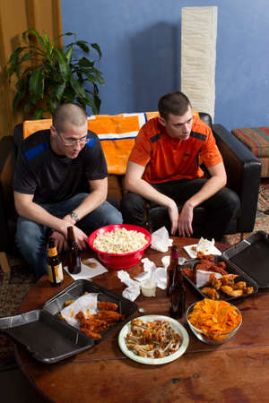 Two men disappointed while watching sports game on TV, vertical photo