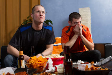 Two men anxious while watching game, horizontal photo