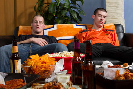 Two tired men on couch after watching game, horizontal photo