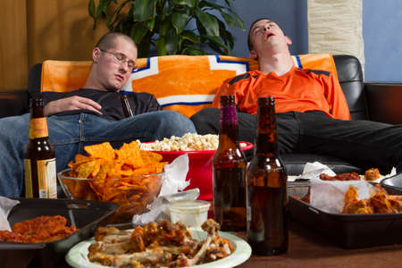 Two men passed out on couch after watching game, horizontal