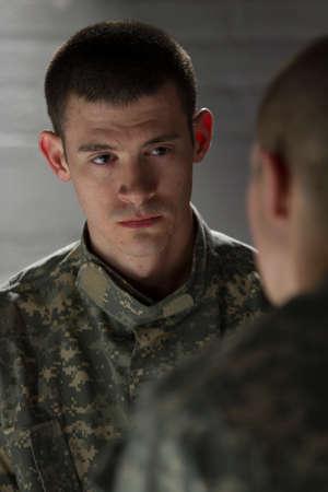 Soldier meeting with peer in dark room, vertical Stock Photo