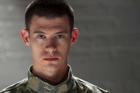 Military man looks serious in dark room, horizontal Stock Photo