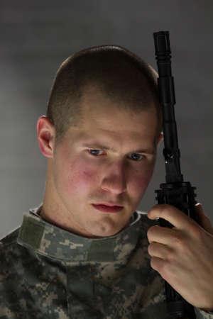 Sad soldier resting head on assault rifle, vertical
