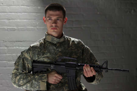 assault rifle: Military man holding assault rifle, horizontal Stock Photo